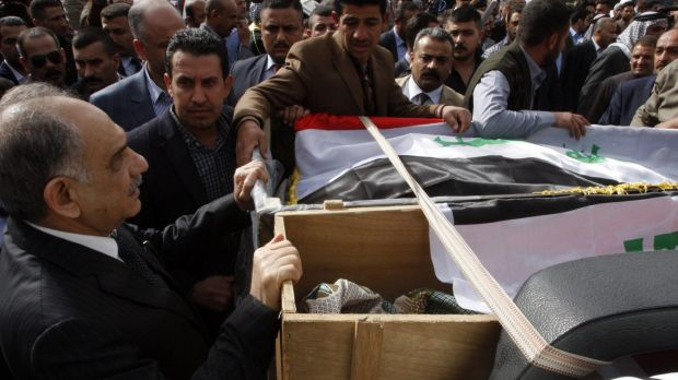 Iraqi Deputy Prime Minister Saleh al-Mutlaq (left) holds on to the coffins during the funeral of Sheikh Qasim al-Janabi ...