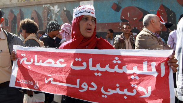 Yemenis shout slogans during a rally against the occupation of the capital by the Shiite Houthi movement. The woman's ...