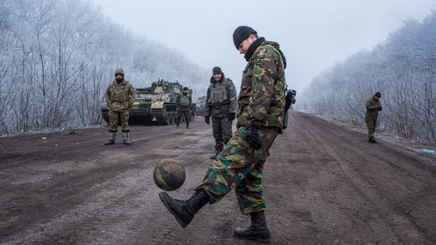 Ukrainian soldiers play football on the road leading to the embattled town of Debaltseve. The Ukrainian forces say they ...