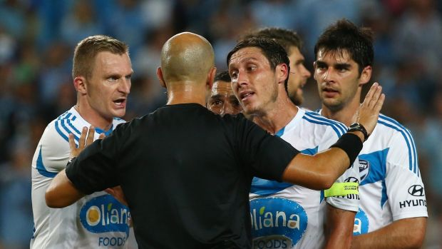 Besart Berisha and Mark Milligan of Melbourne Victory argue with referee Strebre Dilovski after he awarded a penalty.
