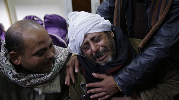 Grief ... A man is comforted as he mourns the Egyptian Coptic Christians who were captured in Libya and beheaded by ...