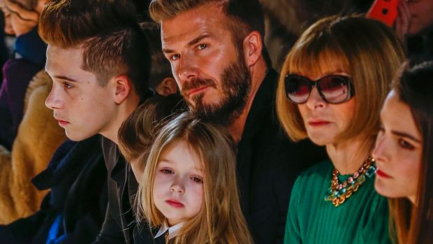 David Beckham sits next to Anna Wintour with his daughter, Harper, on his lap, and son Brooklyn during a presentation of ...