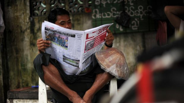 A Myanmar man reads a local newspaper in Yangon.