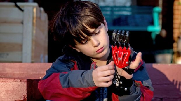 Ethan Brown, 8, was born with two fingers missing on his left hand. Now he wears a Cyborg Beast in black and red, his ...