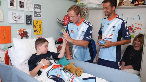 Easing the blues: Rhyan Grant and Alex Brosque present hospitalised fan Zachary Chidiac with a team shirt.
