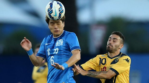 On top: Wang Song of Guangzhou heads the ball over Anthony Caceres of the Mariners.