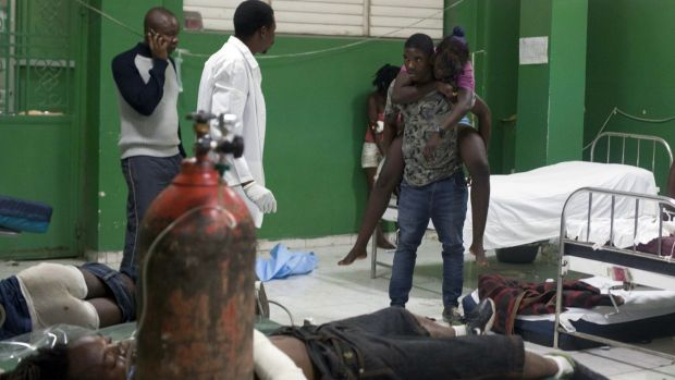 An injured woman is carried by a friend in the emergency room of the General Hospital in Port-au-Prince, Haiti, after ...