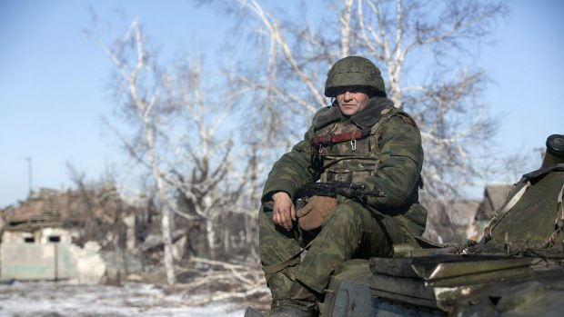 A fighter with separatist self-proclaimed Donetsk People's Republic army sits on top of an armoured personnel carrier in ...