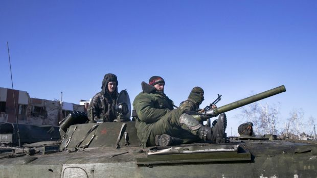 Fighters with separatist self-proclaimed Donetsk People's Republic army sit on top of an armoured personnel carrier as ...