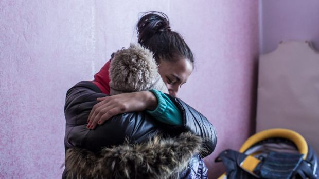 Two women share a hug at a distribution point for humanitarian aid at the local House of Culture in Myronivskyi, Ukraine.