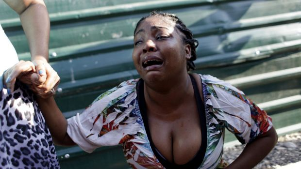A woman cries after a family member was killed when a carnival float hit power lines in Port-au-Prince. At least 18 ...
