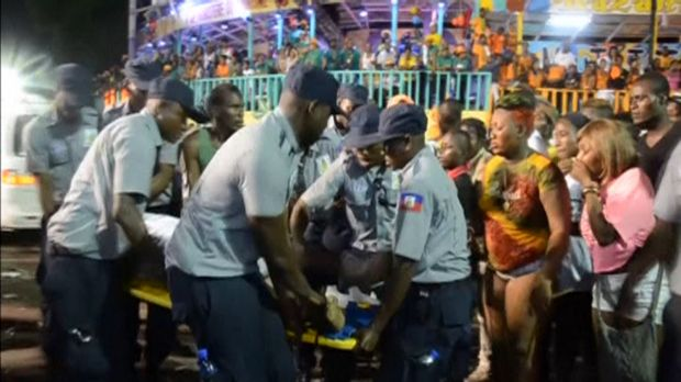 People look at an injured person being carried away after a carnival float hit power lines during the annual Carnival ...