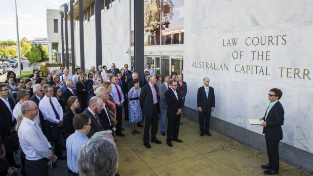 ACT Bar Association president Shane Gill, right, leads members of the legal profession in a minute's silence outside the ...