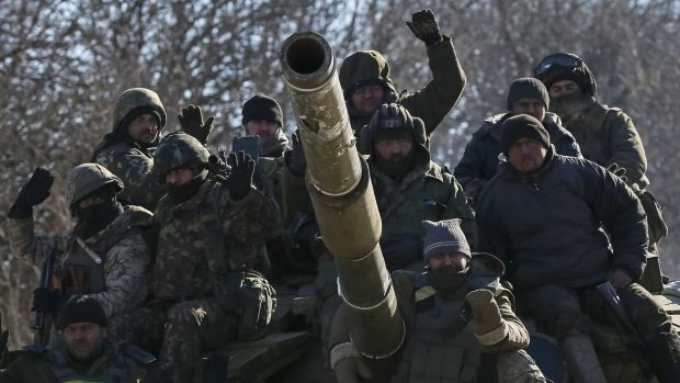 Ukrainian servicemen ride on a tank as they leave the area around Debaltseve in eastern Ukraine.