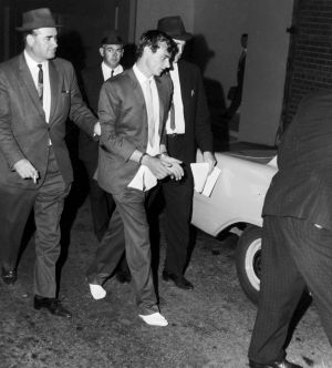 Peter Walker is led in to police headquarters in Sydney after his recapture in January 1966.