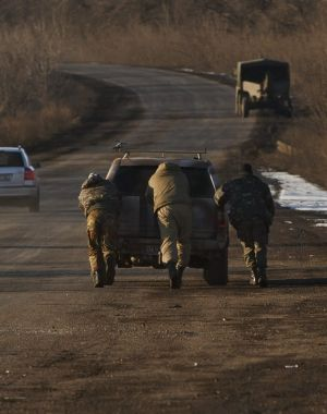 Ukrainian troops push a car  outside Artemivsk, Ukraine, while pulling out of Debaltseve.