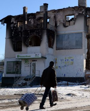 A man walks past a damaged building in Uglegorsk, six kilometres south-west of Debaltseve.