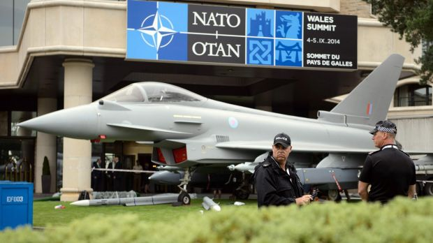Police officers stand near a model of a Typhoon fighter jet ahead of the NATO summit in Wales last year.