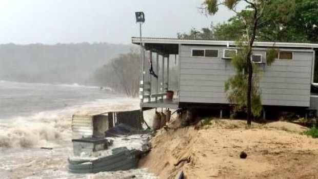 A home gradually collapses off a sandback on Great Keppel Island as Tropical Cyclone Marcia approaches the coast.