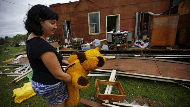 Melanie Cobb holds her childhood teddy bear she retrieved from her grandmother's damaged home after Cyclone Marcia hit ...