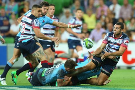 Jack Debreczeni of the Rebels passes as he is tackled by Bernard Foley of the Waratahs.