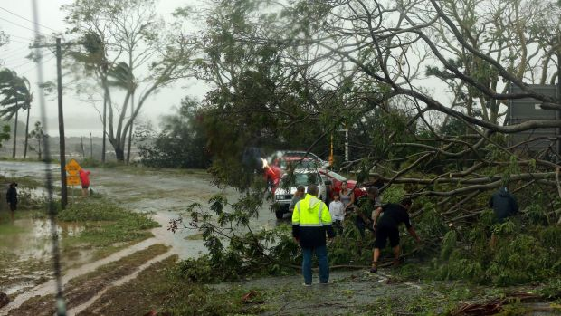 Residents try to clear a road blocked by uprooted trees after Tropical Cyclone Marcia hit the coastal town of Yeppoon in ...