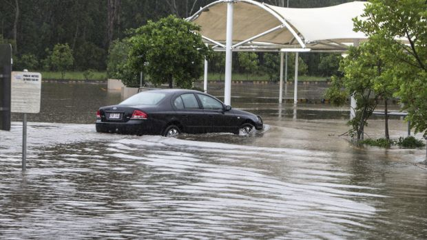A car navigates flooding in a Burpengary shopping centre carpark in Brisbane on Friday.