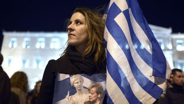 A woman holds a Greek flag and a placard depicting the German chancellor Angela Merkel during a demonstration in front ...