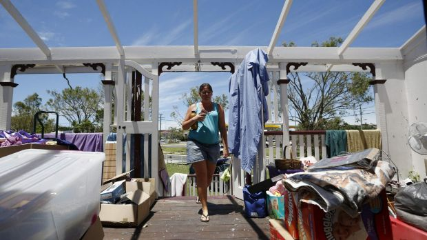 Yeppoon resident Demelza Bischoff walks onto the roofless veranda of her home on Saturday, after it was damaged during ...