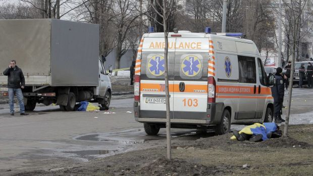 Ukrainian national flags cover the bodies of the victims of Sunday's bomb attacks in Kharkiv.