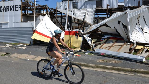 A resident rides past a cyclone damaged business in Rockhampton.
