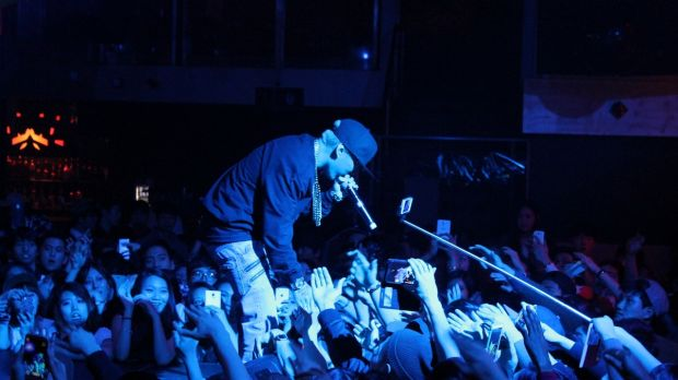 A music fan using a selfie stick at a concert in Toronto, Canada.