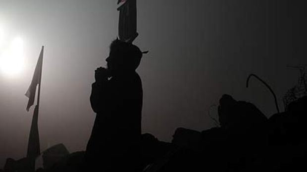 A relative of a trapped miner prays.