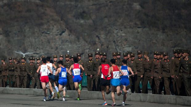 Marathon runners pass by a long row of North Korean soldiers during the Pyongyang marathon in 2013.