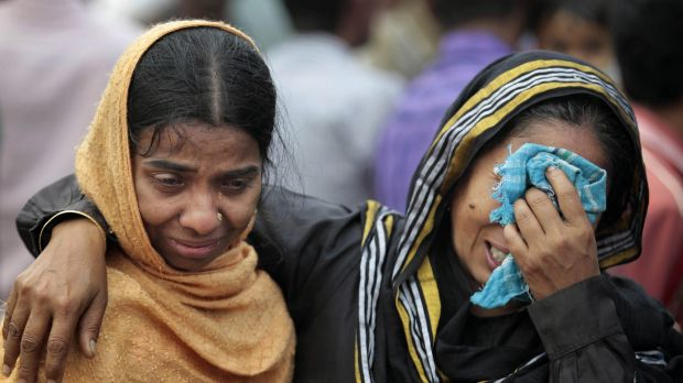 Bangladeshi people cry as rescuers search the River Padma after a passenger ferry sank after colliding with a cargo boat.
