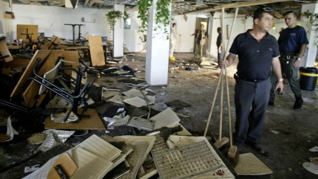 In this July 31, 2002 photo, workers clean the inside of a cafeteria hours after a bomb exploded at Hebrew University in ...