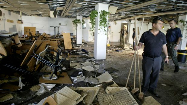 July 2002: workers clean the inside of a cafeteria hours after a bomb exploded at the Hebrew University in Jerusalem, ...