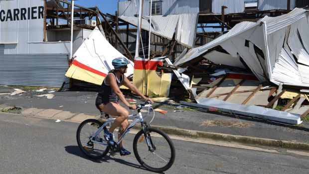 A resident cycling past a cyclone damaged business in the northern Queensland town of Rockhampton after Cyclone Marcia hit.