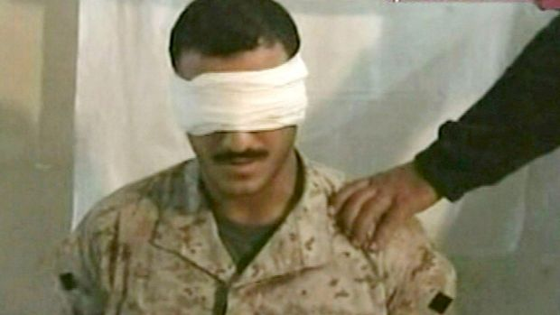 A screenshot of the video aired by Al Jazeera on June 27, 2004 shows a blindfolded man dressed in camouflage sitting in ...