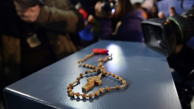 Rosary beads and a poppy are shown at a news conference in Toronto, Ontario.