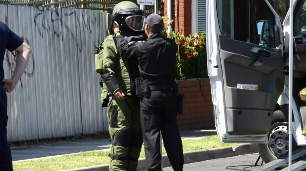 A member of the bomb squad investigates after possible explosives were handed in to St Kilda Police Station.