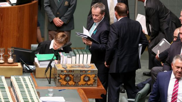 Opposition Leader Bill Shorten tries to squeeze past Prime Minister Tony Abbott to get back to his seat, after a ...