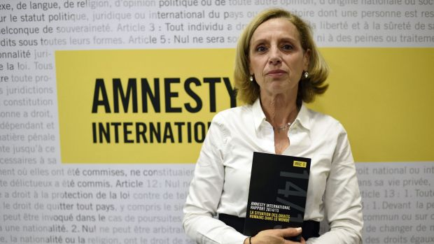 Amnesty International France President Genevieve Garrigos holds a copy of the 415-page annual report, which details ...