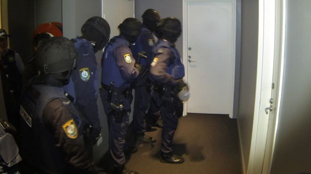 Police carry out one of the early morning raids.