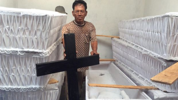 Undertaker Suhendro Putro's assistant, Sulamin, with the extra coffins ordered for the executions.