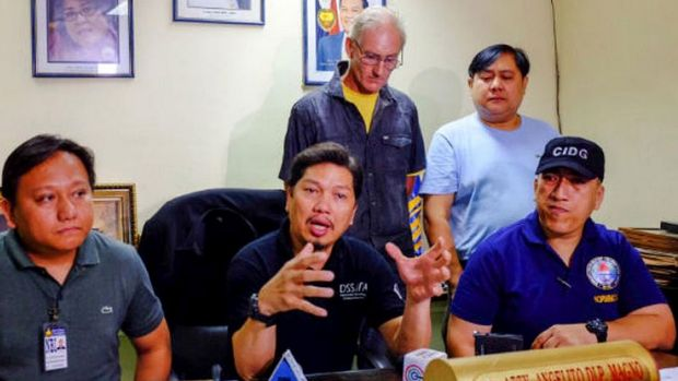 Alleged Australian sex offender Peter Gerard Scully stands behind Philippines police investigator Angelito Magno