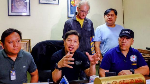 Alleged Australian sex offender Peter Gerard Scully stands behind Philippines police investigator Angelito Magno.