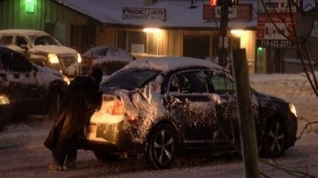 Homeless man Shelby Hudgens helps push stricken cars during a snow storm in Colorado Springs.