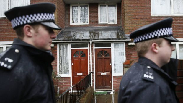 Two police officers walk outside a flat in London  flat that is the former home of Mohammed Emwazi.