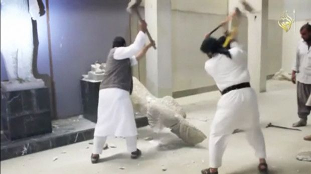Men use sledgehammers on a toppled statue in a museum at a location said to be Mosul in this still image taken from an ...